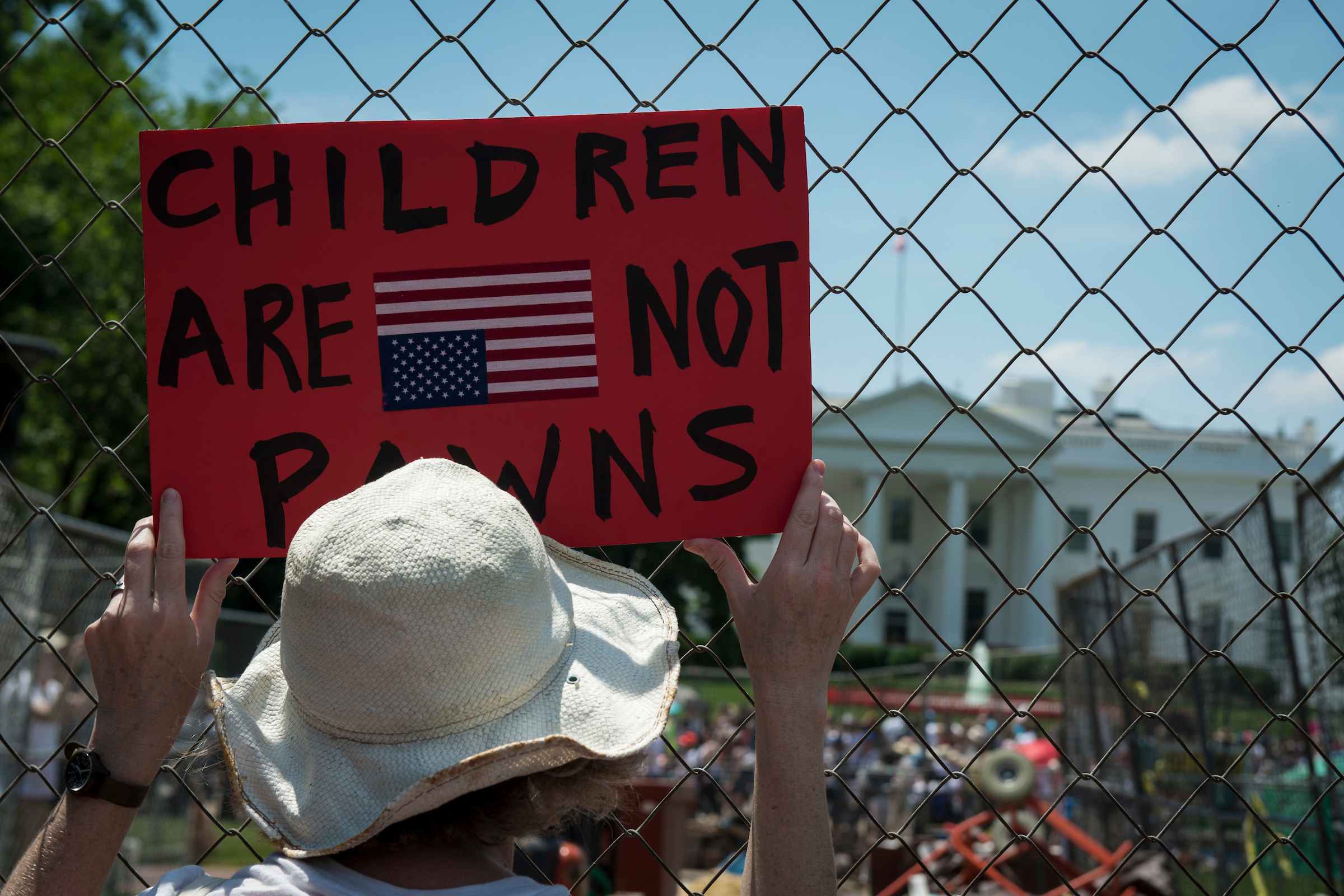 A woman holds a sign during a Families Belong Together protest outside the White House in June.  (Sarah Silbiger/CQ Roll Call)