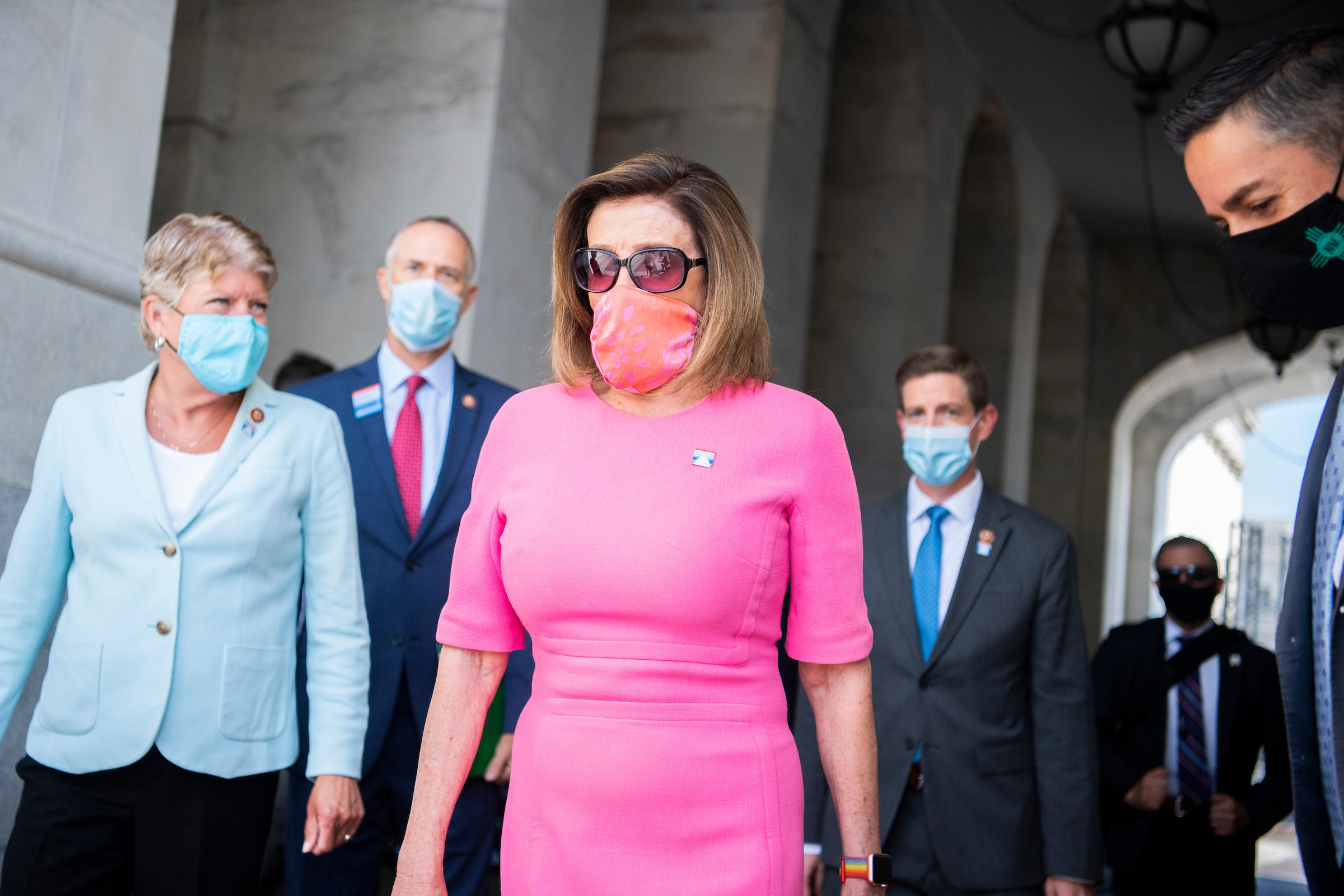 Speaker Nancy Pelosi, D-Calif., makes her way to a news conference on the House steps with members of the House Select Committee on the Climate Crisis, Tuesday, June 30, 2020. Also appearing are, from left, Reps. Julia Brownley, D-Calif., Jared Huffman, D-Calif., Mike Levin, D-Calif., and Ben Ray Lujan, D-N.M., far right. (Tom Williams/CQ Roll Call)