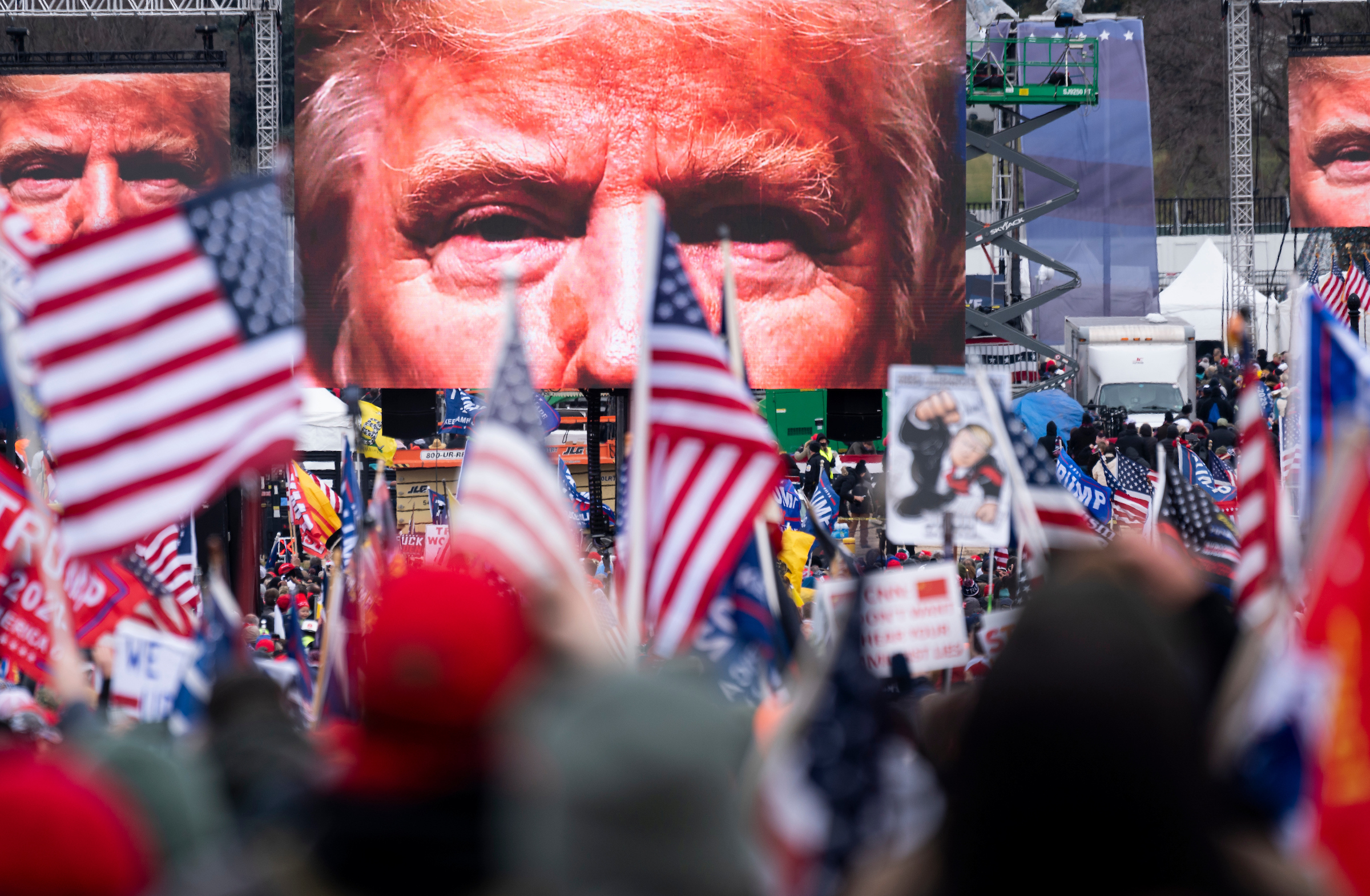 An image of President Donald Trump appears on video screens before his speech to supporters near the White House on Jan. 6. (Bill Clark/CQ Roll Call file photo)