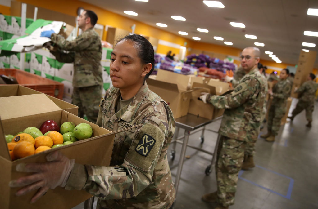 Members of the California National Guard 115th Regional Support Group help pack boxes of fruit and other food at the Second Harvest Food Bank of Silicon Valley on March 24, 2020, in San Jose, Calif. (Justin Sullivan/Getty Images file photo)